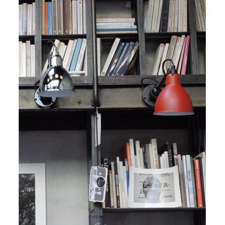 Wandspot La Lampe Gras op de boekenkast, links een verchroomde kap en rechts een gematteerde rode kap